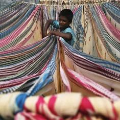 Een foto van een jongetje dat tussen groten doeken staat.
