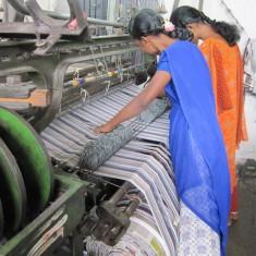 Een foto van 2 vrouwen die bij een weefmachine staan.