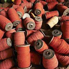 Een foto van allemaal rolletjes rode garen.