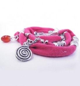 Handgemaakte armband: wikkelarmband met vele bedeltjes over de gehele armband in de kleur roze.