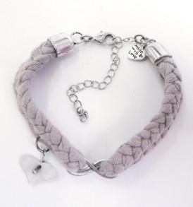 Handgemaakte armband: gevlochten armband met bedeltje in het midden en een hartje aan een zijde in de kleur beige.
