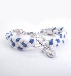 Handgemaakte armband: gevlochten armband met bedeltje in het midden in de kleur blauw/wit.