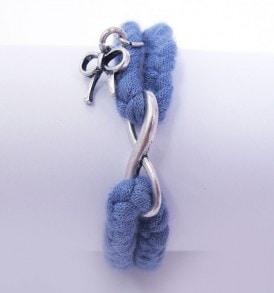 Handgemaakte armband: gevlochten armband met bedeltje in het midden en een strikje aan een zijkant in de kleur blauw.