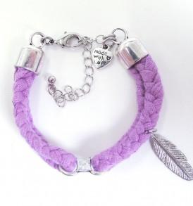Handgemaakte armband: gevlochten armband met bedeltje in het midden en een veertje aan de zijkant in de kleur paars.