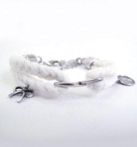 Handgemaakte armband: gevlochten armband met bedeltje in het midden en aan beide zijde in de kleur wit.
